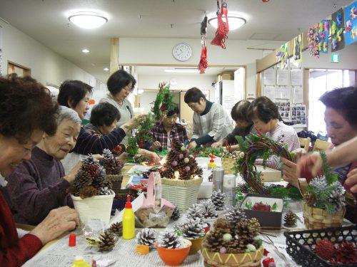 約10人の女性がテーブルを囲みクリスマスリースを作っている様子