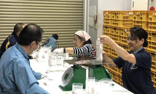 男女4人がプラントで製造されたリサイクル石けんを軽量し袋詰め作業をしている様子