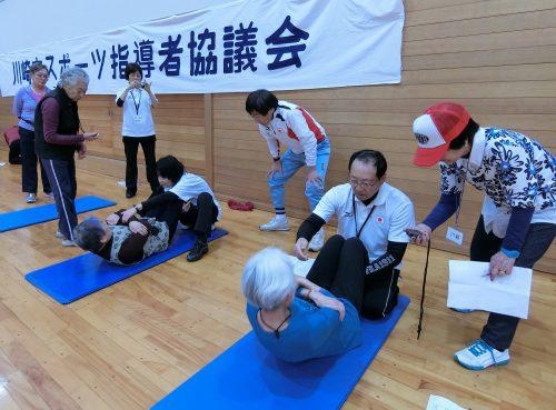 腹筋運動をする女性らとそれをサポートする会員の写真