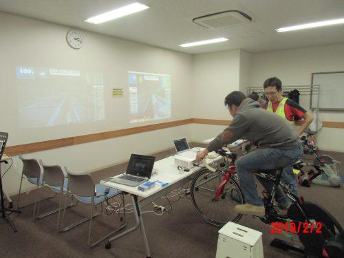 固定したロードバイクをこぐと目の前の映像により実際に外を走っている体験ができる様子の写真