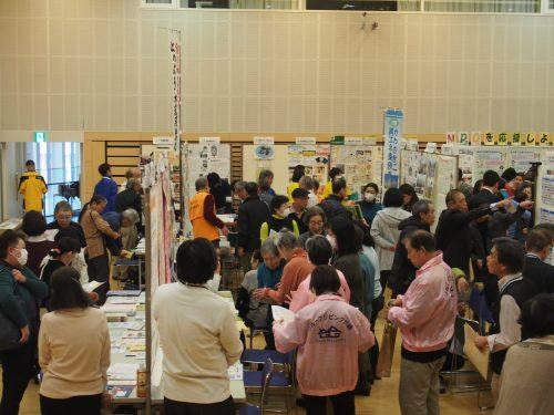 中原市民館ホール内、たくさんのパネルに団体の活動が紹介されており、たくさんの人が話をしている写真