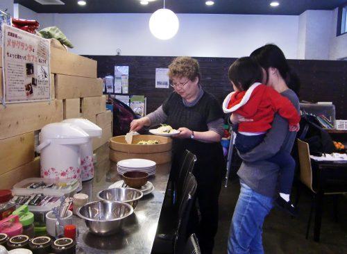子どもを抱きかかえた女性に料理の盛りつけを手伝うメンバーの様子の写真