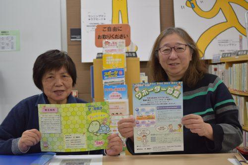チラシを持ち笑顔を浮かべる団体メンバーの写真
