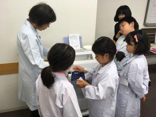 白衣を着て薬の分包を体験する4人の子どもとその指導にあたる女性の写真