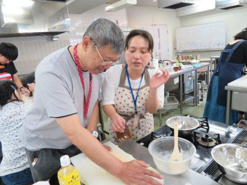 調理室でパン作りをしている男性とその指導をする女性の写真