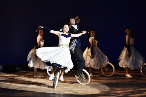 華やかな衣装で一輪車に乗り演技をしている5人の男女の写真