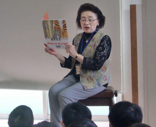 子どもたちの前に座り絵本の読み聞かせをしている女性の写真