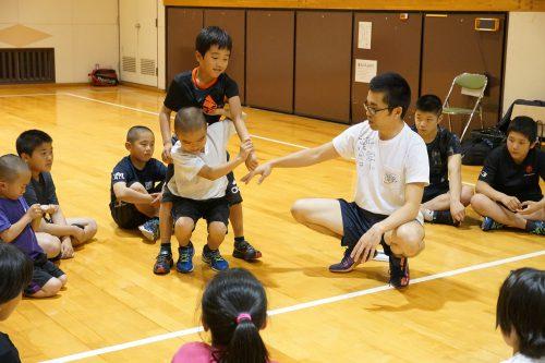 輪になって座る子供たちの中心で男性が背負い投げの指導をしている様子