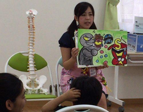 背骨の骨格標本を横に置き、子ども達に手作りの紙芝居を披露する女性の写真