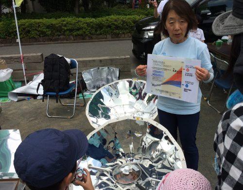 パラボラ型のソーラークッカーを前に置き、資料を手に持ち子どもたちに説明をする女性の写真