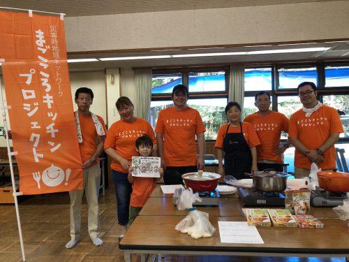 食材や調理器具を置いた机を前に団体ののぼりを立て揃いのTシャツを着て並ぶ団体メンバーの男女7人の写真