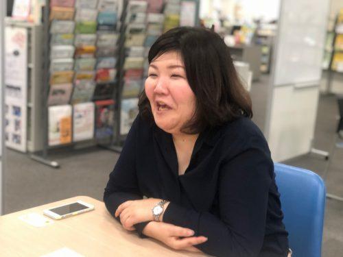 テーブルにつき笑顔でインタビューに応じる女性の写真