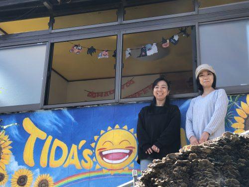 空き家をリフォームして作ったコミュニティハウスの前に立つ代表の女性ら2人の写真