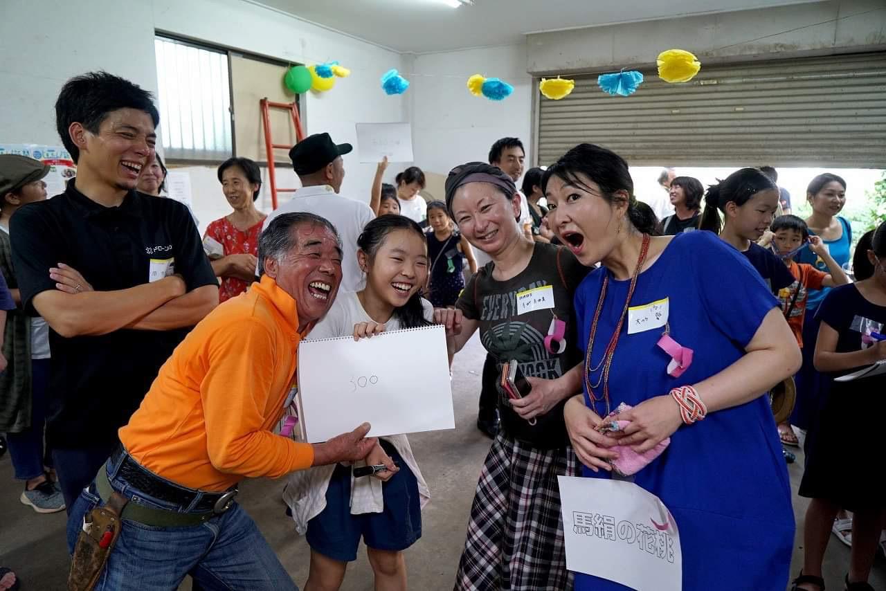 子ども記者を大人が囲んで笑顔の写真